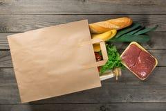 Nourriture différente dans le sac de papier sur le fond en bois Images stock