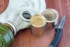 Nourriture en boîte et un couteau avec un masque de gaz en cas d'attaques de gaz, équipement de protection personnel Images stock