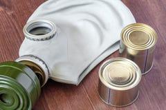 Nourriture en boîte et un masque de gaz sur la table en bois Photos libres de droits