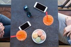 Nourriture et téléphones sur une table tandis que parler de personnes Image stock