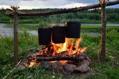 Nourriture faisant cuire sur le feu de camp Image stock