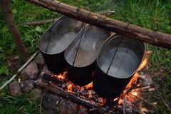 Nourriture faisant cuire sur le feu de camp Photographie stock libre de droits