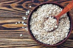 Nourriture Farine d'avoine sur la table Séchez la farine d'avoine de flocons d'avoine roulée dans la cuvette brune sur la vieille Image libre de droits