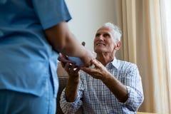 Nourriture femelle de portion de docteur à l'homme supérieur à la maison de retraite photographie stock libre de droits
