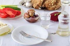 Nourriture grecque, mezedes Pots avec l'huile d'olive et le vinaigre de vigne, olives, feta, tzatziki, pain foncé, raki, betterav Photo stock