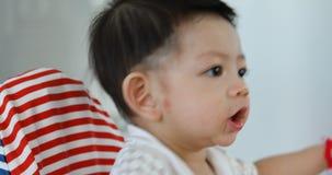 Nourriture heureuse de consommation de bébé garçon avec la maman banque de vidéos