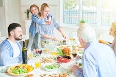 Nourriture heureuse de portion de mère au dîner de famille images stock