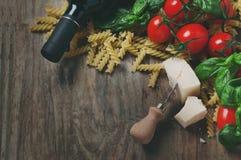 Nourriture italienne avec le fusilli cru, tomate, basilic, fromage Photo stock