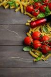 Nourriture italienne - fusilli, tomate, basilic et vin crus sur la table en bois Images libres de droits
