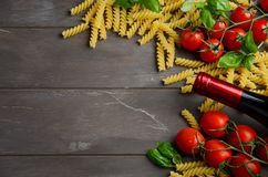 Nourriture italienne - fusilli, tomate, basilic et vin crus sur la table en bois Photo libre de droits