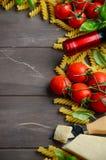 Nourriture italienne - fusilli, tomate, basilic, fromage et vin crus sur la table en bois Photo libre de droits