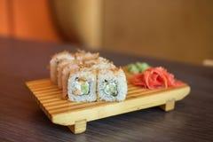 Nourriture japonaise d'un plat en bois des petits pains de sushi avec les poissons et le riz, le gingembre et le wasabi vert Photographie stock