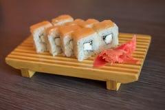 Nourriture japonaise d'un plat en bois des petits pains de sushi avec les poissons et le riz, le gingembre et le wasabi vert Photos libres de droits