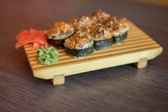 Nourriture japonaise d'un plat en bois des petits pains de sushi avec les poissons et le riz, le gingembre et le wasabi vert Images stock