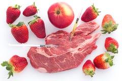Nourriture modifiée pomme, boeuf et fraises sur un fond blanc avec des seringues Photographie stock libre de droits