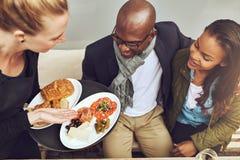 Nourriture plaquée par portion de serveuse aux clients photo libre de droits