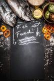 Nourriture pour poissons sur le tableau noir avec les poissons crus de dorado et les ingrédients de légumes et le riz sains, vue  Photographie stock libre de droits