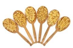 Nourriture sèche par pâtes dans des cuillères en bois de chêne Photographie stock libre de droits