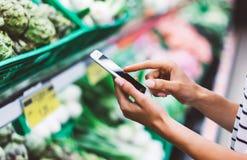 Nourriture saine d'achat d'achats de jeune femme à l'arrière-plan de tache floue de supermarché Fermez-vous vers le haut des prod photos libres de droits