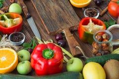 Nourriture saine, sélection propre de nourriture : fruits, légumes, graines, épices sur les conseils bruns Image stock