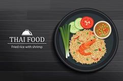 Nourriture thaïlandaise dans le plat sur la vue supérieure en bois noire de table Riz frit avec la crevette illustration libre de droits