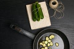 Nourriture végétarienne cuite Frit avec l'huile d'olive a coupé en tranches la courgette sur la casserole sur un bois rugueux Et  Photos libres de droits
