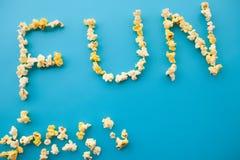 Nourriture Word d'AMUSEMENT Seau de maïs éclaté Maïs éclaté délicieux sur le CCB bleu Images stock