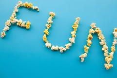 Nourriture Word d'AMUSEMENT Seau de maïs éclaté Maïs éclaté délicieux sur le CCB bleu Photo libre de droits