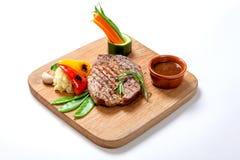 Nourritures grillées - bifteck de boeuf de BBQ avec de la sauce chaude et des légumes sur un conseil en bois Photo stock