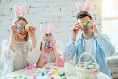 Nous aimons de belles traditions Les oeufs de peinture de maman et de fille, papa tient un lapin décoratif à la maison image libre de droits