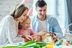 Nous aimons de belles traditions Les oeufs de peinture de maman et de fille, papa tient un lapin décoratif à la maison photo stock
