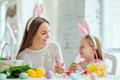 Nous aimons de belles traditions Les oeufs de peinture de maman et de fille, papa tient un lapin décoratif à la maison photos libres de droits