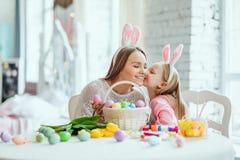 Nous aimons de belles traditions Les oeufs de peinture de maman et de fille, papa tient un lapin décoratif à la maison images stock