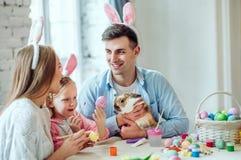 Nous aimons de belles traditions Les oeufs de peinture de maman et de fille, papa tient un lapin décoratif à la maison photos stock
