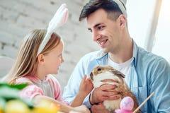 Nous aimons de belles traditions Les oeufs de peinture de maman et de fille, papa tient un lapin décoratif à la maison photo libre de droits