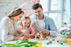 Nous aimons de belles traditions Les oeufs de peinture de maman et de fille, papa tient un lapin décoratif à la maison photographie stock libre de droits