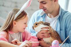 Nous aimons de belles traditions Les oeufs de peinture de maman et de fille, papa tient un lapin décoratif à la maison images libres de droits