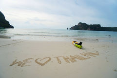 Nous aimons la Thaïlande - textotez écrit à la main en sable sur une plage de mer avec le kayak au-dessus du ciel Photo stock