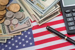 Nous drapeau, billets de banque du dollar, nous pièce de monnaie de cent, stylo et calculatrice Image libre de droits