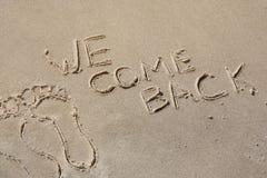 Nous revenons - écrit à la main en sable sur une plage de mer, avec une vague molle Fin du repos, vacances Photo libre de droits