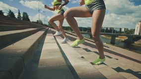 Noutside de las escaleras del atleta de sexo femenino del corredor que sube Las zapatillas deportivas y las piernas se cierran pa metrajes