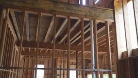 Nouveau bâtiment non fini en dehors de la construction du bois de cadre et de faisceau banque de vidéos