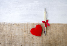 Nouveau cadeau argenté de stylo et coeur rouge sur le tissu hessois au-dessus du fond en bois blanc Photographie stock libre de droits