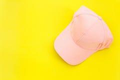 Nouveau chapeau de base-ball rose vide sur le fond jaune avec l'espace libre Photographie stock libre de droits
