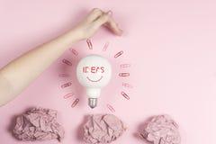 Nouveau concept d'idée avec le papier chiffonné de bureau, main femelle tenant l'ampoule Images stock