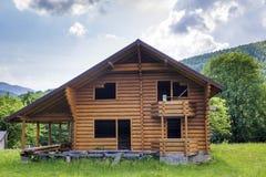 Nouveau cottage écologique en bois avec le balcon, terrasse, toit raide des matériaux naturels en construction sur le pré herbeux photos stock