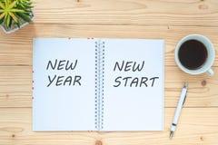 Nouveau début de nouvelle année avec le carnet, la tasse de café noir, le stylo et les verres sur la table, la vue supérieure et  photographie stock libre de droits