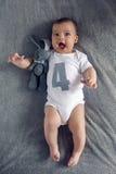 Nouveau-né à quatre mois se trouvant sur le lit Image stock