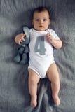 Nouveau-né à quatre mois se trouvant sur le lit Photographie stock