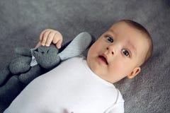 Nouveau-né à trois mois se situant dans le lit Photographie stock